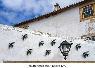 Black small ceramic swallow bird (andorinha) decoration and a small street lamp situated on the wall of house in Obidos, Portugal. The swallow is the Portuguese symbol of a family, love and fidelity.