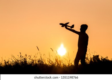 Black small silhouette of young happy kid playing toy plane outdoors at sunset time. Horizontal color photography.
