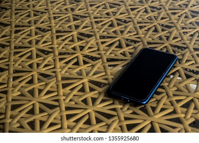 Black smart phone with blank screen put down on modern table with ratten background