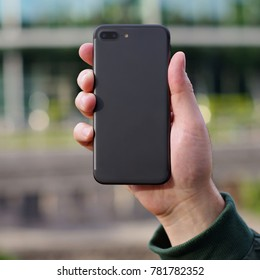 Black smart phone in a man's hand back view on a blurry city background. Template of phone case