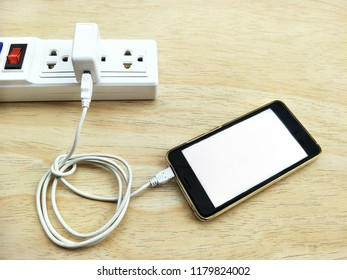 Black smart phone, white adaptor, white extension lead on wooden table floor in charging mobile phone system, high angle view with copy space