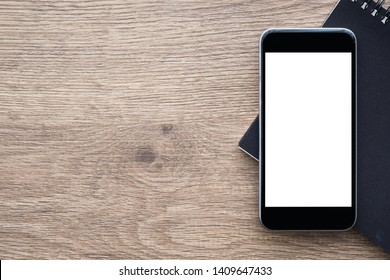Black smartphone with blank screen is on top of notebook over wood office desk table. Top view with copy space, flat lay.