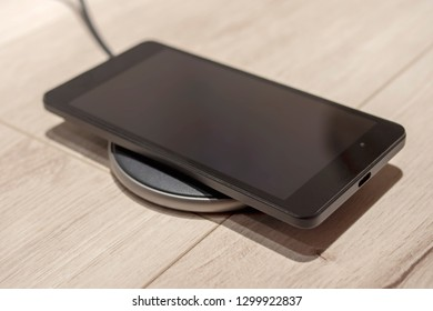 Black smartphone charging on a wireless charging pad