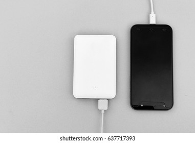 A black smartphone charging with a white powerbank set on gray background. Selective focus with copy space.