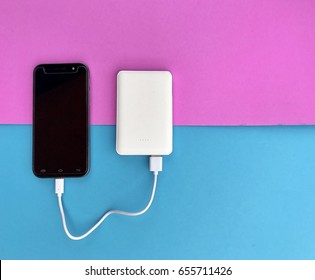 A black smartphone charging with white powerbank on pink and blue background. Top view with copy space. Selective focus.