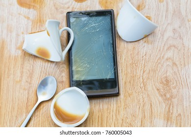 Black Smartphone falls to the ground with broken and coffee spilled on wooden floor