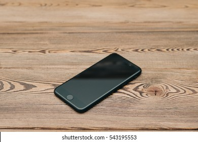 Black smartphone lying on a wooden table