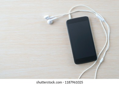 Black smartphone with white headphones on a beige board.
