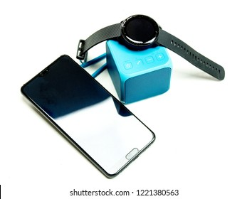 Black smartwatch on top of blue bluetooth wireless speaker isolated on white background together with a black smartphone next to the smart watch and speaker.