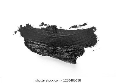 Black smear on white background, charcoal or clay facial mask, beauty and skin care concept