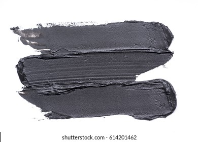 Black smears of mud mask for face on a white background.