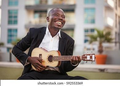 black smiling man wearing formals playing a guitar