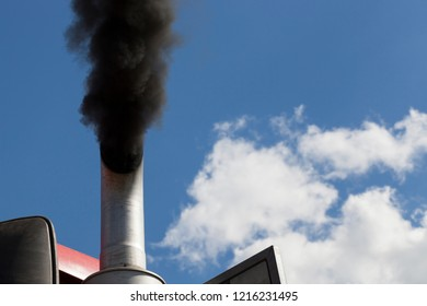 black smoke against the blue sky coming from the exhaust pipe of the tractor during engine operation
