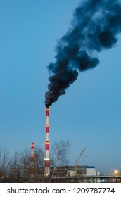 Black smoke from the pipe of a coal boiler contaminates the air.
