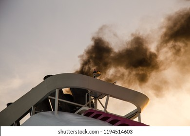 Black smoke from a ship starting its main engines and preparing to leave
