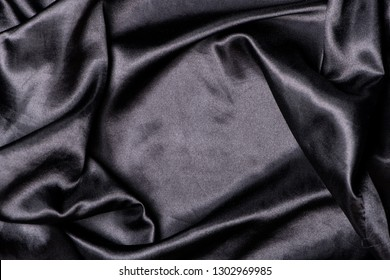 Black smooth elegant satin texture, can be used as abstract design background, fabric pattern