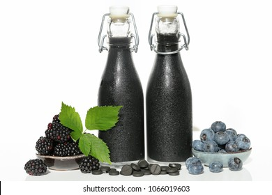 black  smoothie . Healthy smoothie . smoothies of black color from blueberries, blackberries and activated charcoal in tablets on white background with reflection. Super food