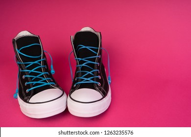 black sneakers with blue headphones instead of laces
