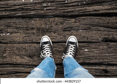 Black sneakers with hipster man on wooden . topview