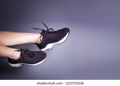 black sneakers and legs on a gray background