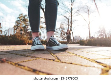 black sneakers on the legs of a woman walking in the park