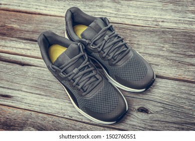 Black sneakers on a wooden background. Toned photo.