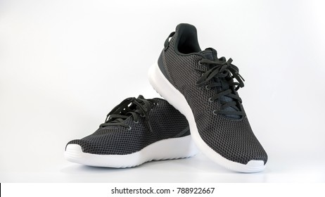 Black sneakers running shoes isolated on white background.