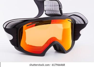 Black snowboard googles with sun orange lens on it in white background
