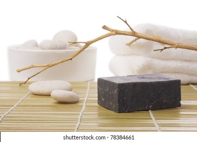 black soap on bamboo mat with stone and towel
