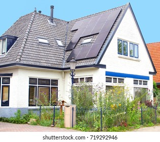 Black solar panels on roof of typical Dutch family house, Netherlands