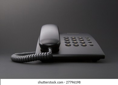 Black solid office phone with cord isolated on black background