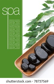 Black Spa massage Stones on wooden tray. Some green leaves on white background. Space for text on green panel.