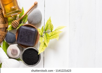 Black spa soap made from activated charcoal and honey on white wooden background, facial and body cleansing product