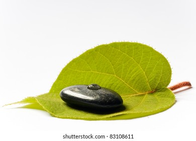 black spa stone with a drop on a green leaf on white ground