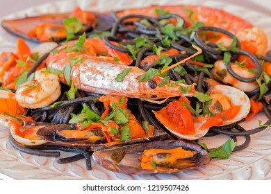 "Black ""spaghetti allo scoglio"" with mussels, clams and king prawns."