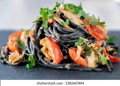 Black spaghetti with cherry tomatoes and tuna and parsley.