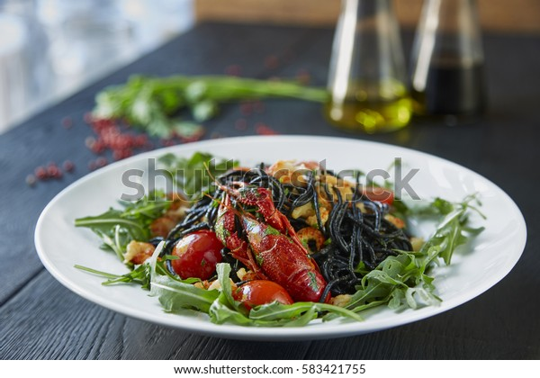 Black spaghetti with crayfish, fresh green arugula, cilantro, pepper and olive oil on a dark wooden table.