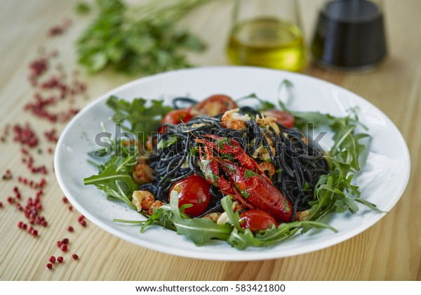 Black spaghetti with crayfish, fresh green arugula, cilantro, pepper and olive oil on a light wooden table.