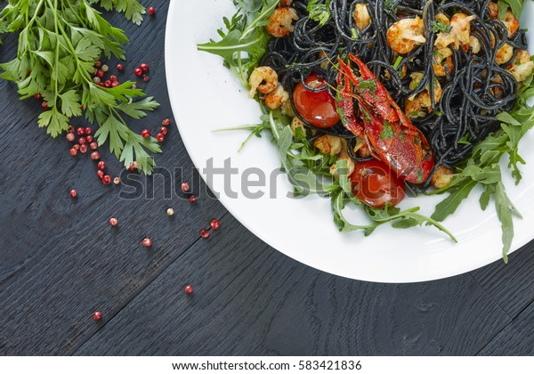 Black spaghetti with crayfish, fresh green arugula, cilantro, pepper and olive oil on a dark wooden table.