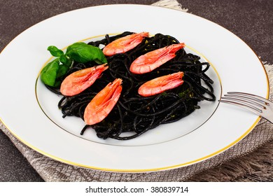 Black Spaghetti with Cuttlefish Ink, Prawns and Basil. Mediterranean and Asian Cuisine. Studio Photo