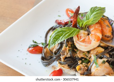 Black spaghetti with seafood on white dish.