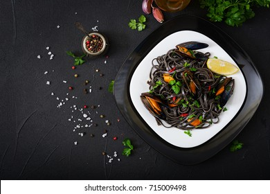 Black spaghetti. Black seafood pasta with mussels over black background. Mediterranean delicacy food. Flat lay. Top view
