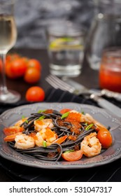 Black spaghetti with shrimps and red caviar on dark background