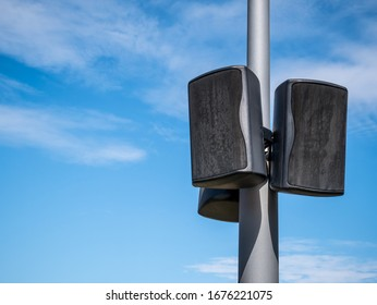 Black speakers suspended from a metal pole with blue sky as a background. Outdoor speakers for music .