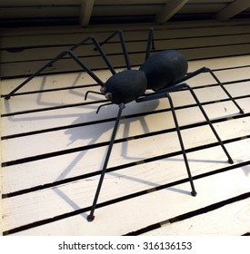 Black spider constructed from metal crawling under the eves