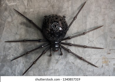 Black spider made of reused metal of gear and vehicle part on gray concrete wall