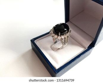Black spinal egg shape ring surrounded by diamond in blue jewel box side view on white background.