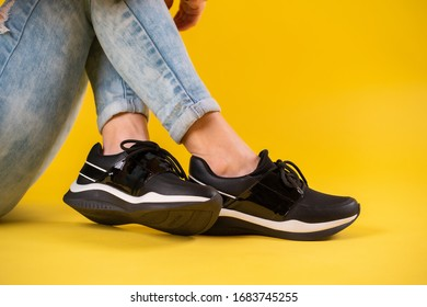 Black sport shoes on young woman with blue jeans and yellow background posing