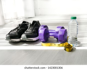 Black sport shoes and sportwear, dumbbells measuring tape and a bottle of water with window light.  Sport lifstyle concept