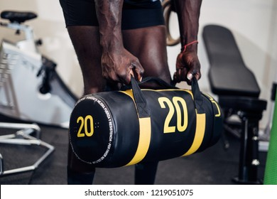 Black sporty young man working out with sandbag while exercises in the gym. Attractive athletic male doing hard workout with weight training. Sport.